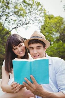 Młoda para siedzi na zewnątrz i czyta powieść