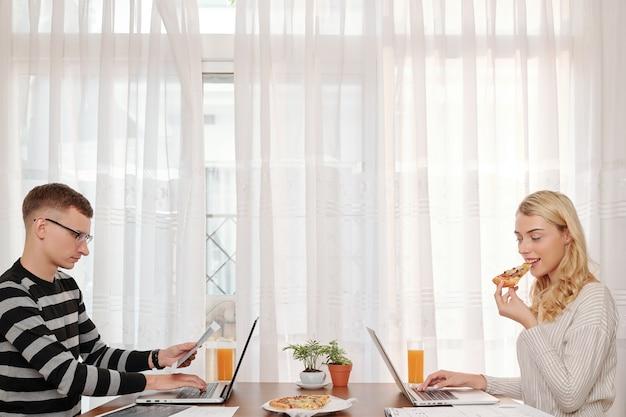 Młoda para siedzi przy dużym stole w domu, je pizzę i pracuje na laptopach