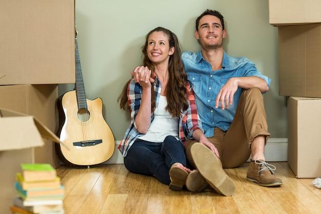 Młoda para siedzi razem na podłodze i uśmiecha się w ich nowej hous