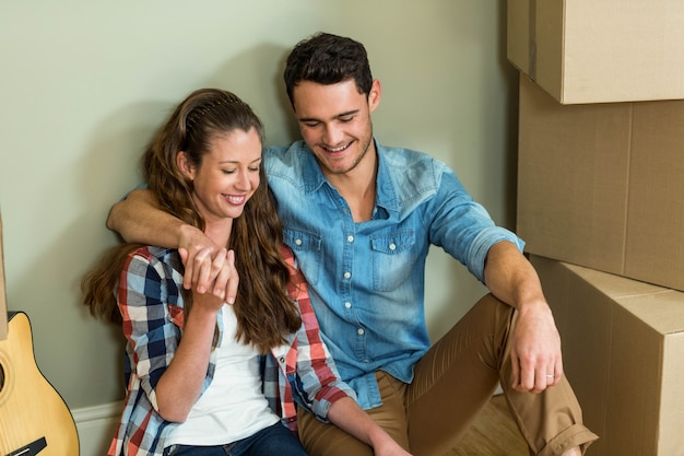 Młoda para siedzi razem na podłodze i uśmiecha się w ich nowym domu