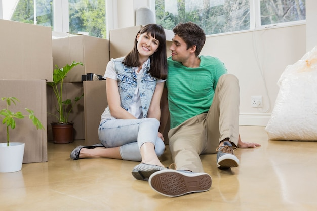 Młoda para siedzi razem na podłodze i uśmiecha się w swoim nowym domu