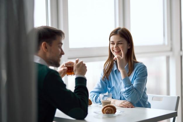 Młoda para siedzi w kawiarni, rozmawiając i pijąc