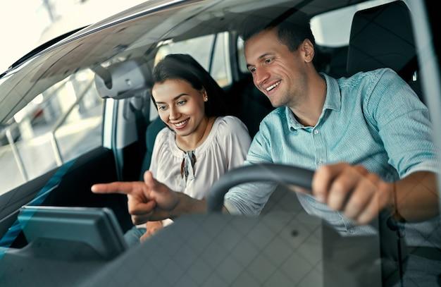 Młoda para siedzi w nowym samochodzie i ogląda go. kupowanie i wypożyczanie samochodów w salonie samochodowym.