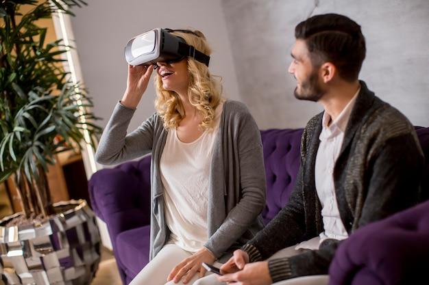 Młoda para siedzi w pokoju, podczas gdy młoda kobieta ma okulary wirtualnej rzeczywistości