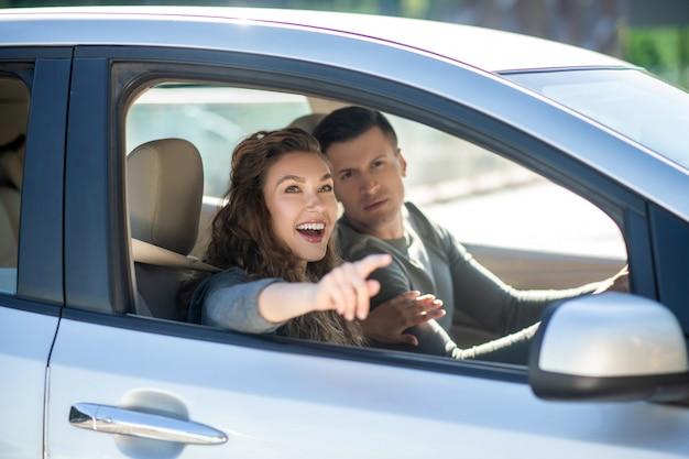 Młoda para siedzi w samochodzie i patrzy na coś