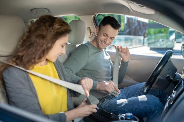 Młoda para siedzi w samochodzie, kobieta ustalająca jej pas bezpieczeństwa