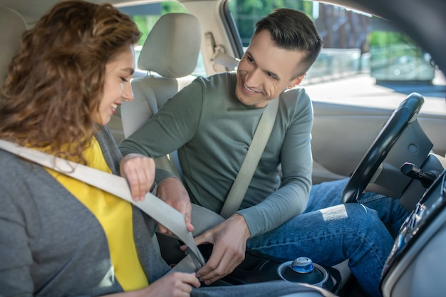 Młoda para siedzi w samochodzie, mężczyzna mocowanie pasa bezpieczeństwa żony