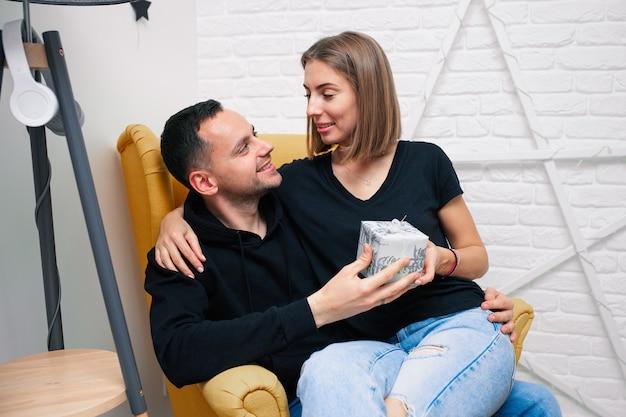 Młoda para siedzi w żółtym fotelu z teraźniejszości