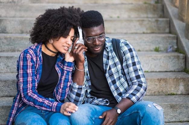 Młoda para słucha muzyki ze wspólnych słuchawek w przyjaźni i związku