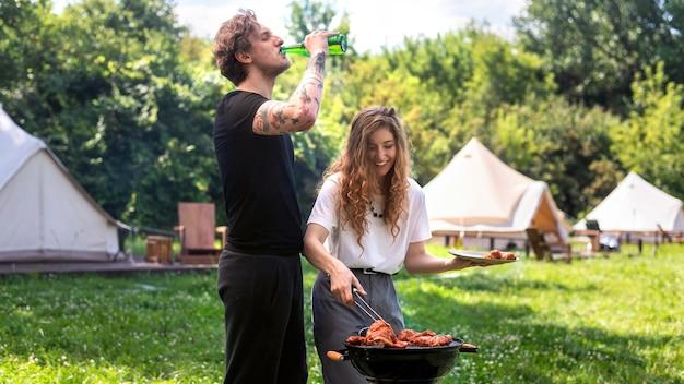 Młoda para smażenia mięsa z grilla i picia piwa. wokół zieleń. glamping
