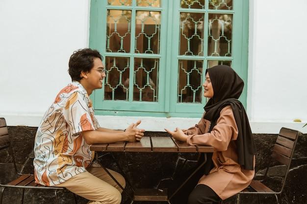 Młoda para śmieje się podczas rozmowy twarzą w twarz