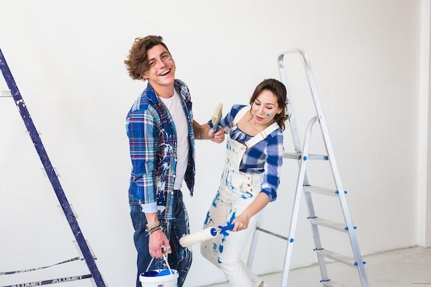 Młoda para śmieszne robi remont w nowym mieszkaniu.
