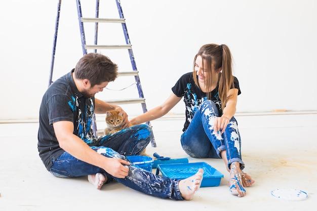 Młoda para śmieszne z kotem robi remont w nowym mieszkaniu.