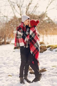 Młoda para sobie koc na śnieżnym polu