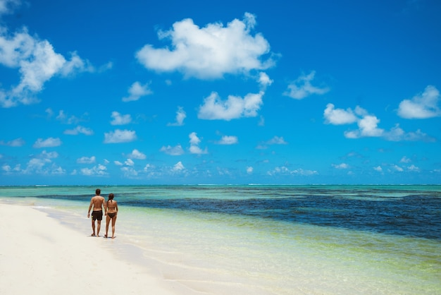 Młoda para spaceru wzdłuż wybrzeża, trzymając się za ręce, z tyłu