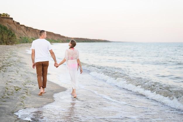 Młoda para spacery ręce wzdłuż wybrzeża morskiego. widok z tyłu