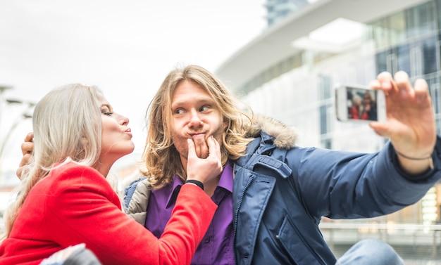 Młoda para spędza czas po południu w centrum mediolanu i robi selfie