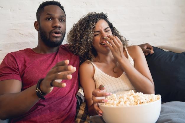 Młoda para spędza razem czas i ogląda seriale lub filmy siedząc na kanapie w domu.