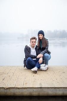 Młoda para spędza razem czas nad jeziorem gebart w mglisty zimowy dzień w zalaegerszeg na węgrzech