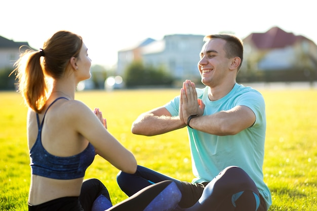 Młoda para sprawny robi ćwiczenia jogi fitness na ciepły letni dzień na świeżym powietrzu.