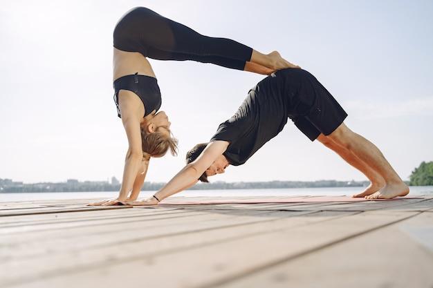 Młoda para sprawny robi joga fitness. ludzie nad wodą.