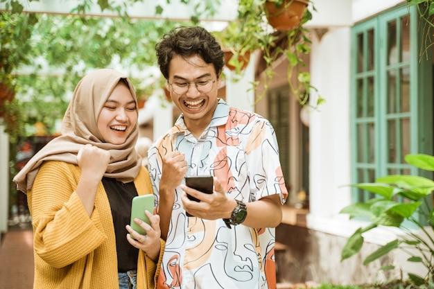 Młoda Para Stała śmiejąc Się, Gdy Zobaczyli Telefon Premium Zdjęcia