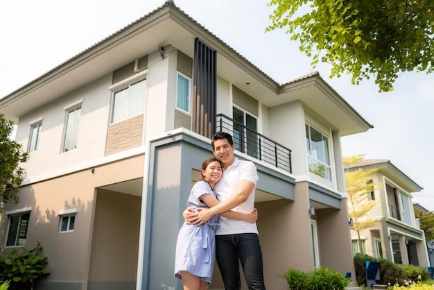 Młoda para stoi i przytulanie razem patrząc szczęśliwy przed ich nowym domem