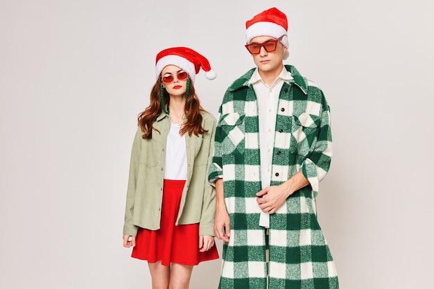 Młoda para stoi obok siebie w świątecznych czapkach