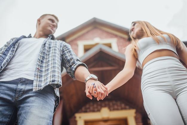 Młoda para stoi przed domem i trzyma się za ręce