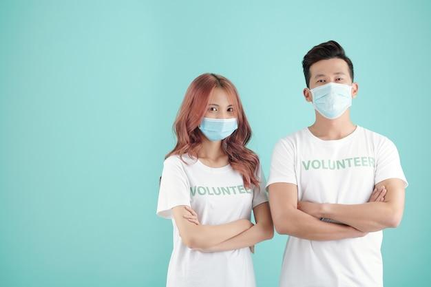 Młoda para stoi w ochronnych maskach i koszulkach wolontariuszy, krzyżując ręce i patrząc na kamerę