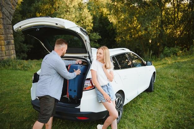 Młoda para stoi w pobliżu otwartego bagażnika samochodu z walizkami, patrząc w kamerę, na zewnątrz