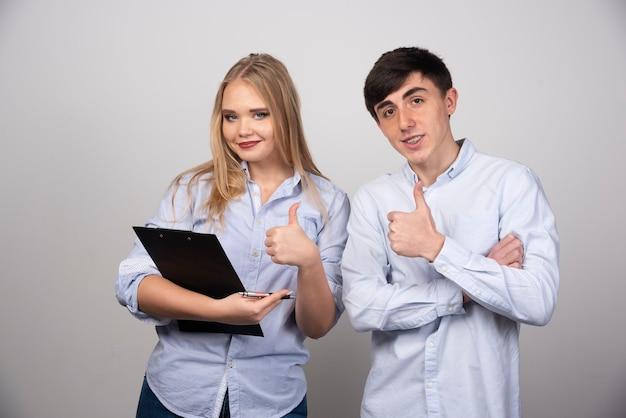 Młoda para stojąc i pokazując kciuk do góry przed szarą ścianą.