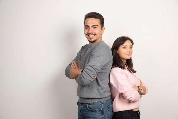 Młoda para stojących ramion skrzyżowanych na białym tle.