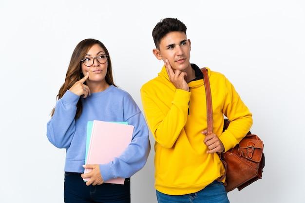 Młoda para studentów na biały myśli pomysł, patrząc w górę