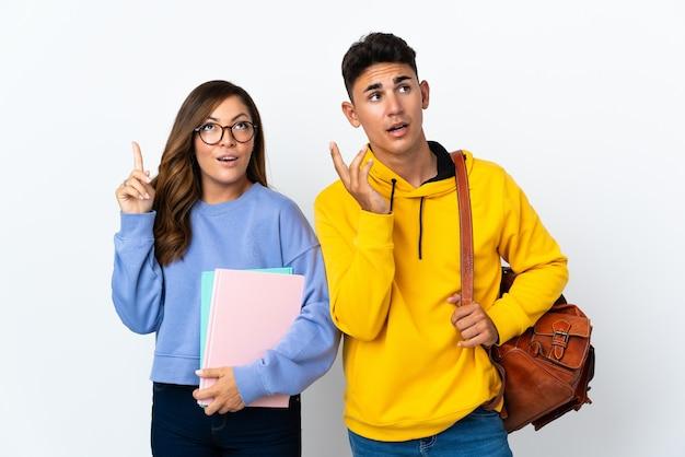 Młoda para studentów na biały myśli pomysł, wskazując palcem w górę