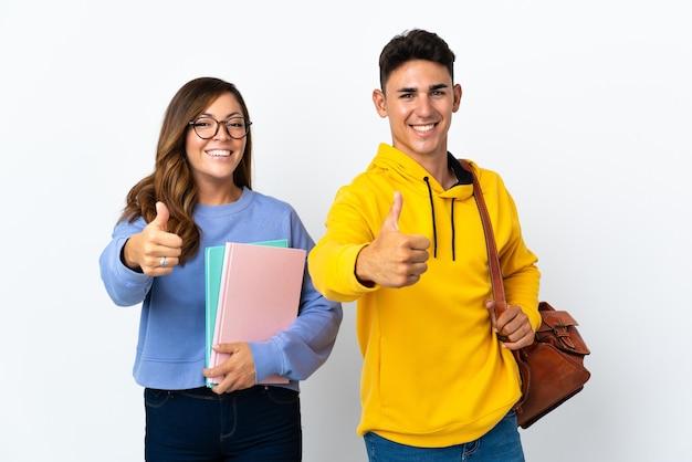Młoda para studentów na białym, dając kciuki do góry gest, ponieważ stało się coś dobrego