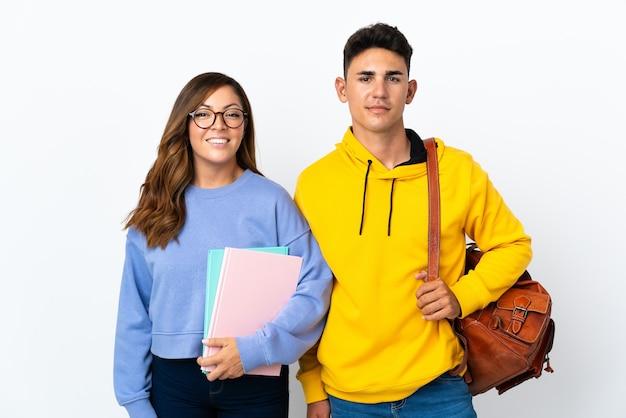 Młoda para studentów na białym pozowanie z rękami na biodrze i uśmiechnięty