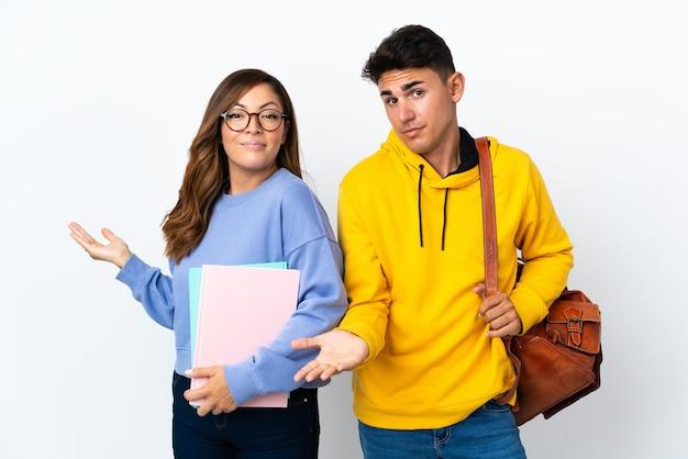 Młoda para studentów na białym tle, mając wątpliwości podczas podnoszenia rąk i ramion