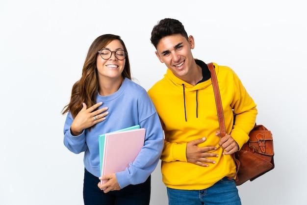 Młoda para studentów na białym tle uśmiecha się dużo, kładąc ręce na piersi