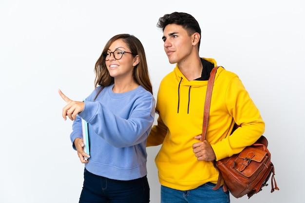 Młoda para studentów na białym tle, wskazując na bok, aby przedstawić produkt