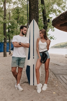 Młoda para stylowe na sobie koszulki i szorty spaceru na zewnątrz w parku w pobliżu deski surfingowej