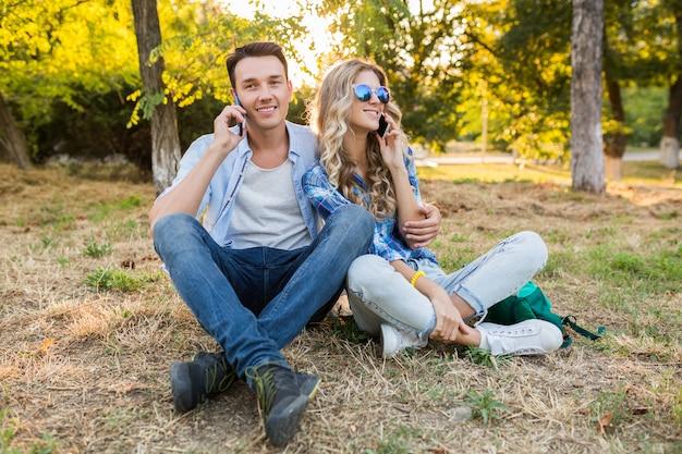 Młoda para stylowe siedzi w parku, mężczyzna i kobieta szczęśliwa rodzina razem