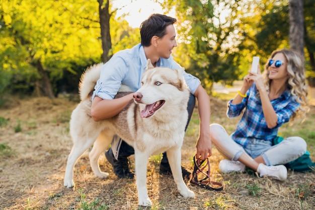 Młoda para stylowy spaceru z psem na ulicy. mężczyzna i kobieta szczęśliwy wraz z rasą husky