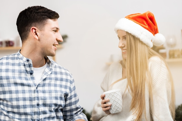 Młoda para świąteczna spędzająca czas razem w pokoju, z bliska