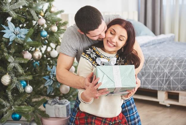 Młoda para świętuje boże narodzenie. mężczyzna nagle podarował żonie prezent. pojęcie szczęścia i dobrego samopoczucia rodziny