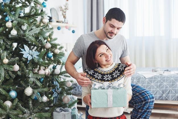 Młoda para świętuje boże narodzenie. mężczyzna nagle podarował żonie prezent.