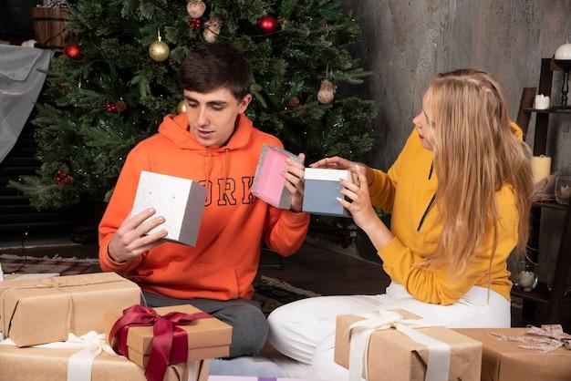 Młoda para świętuje boże narodzenie w domu z prezentami.
