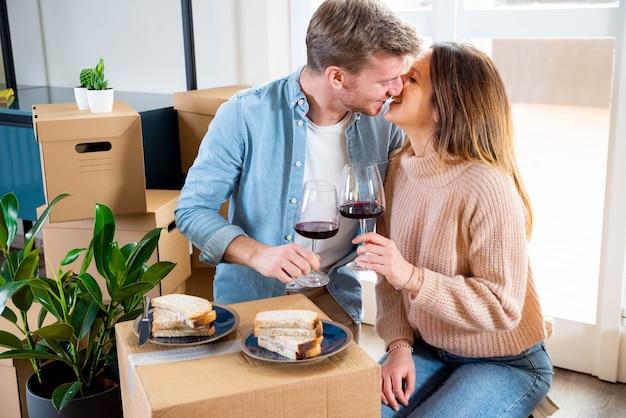Młoda para świętuje zakup nowego domu, pijąc wino na tekturze