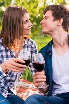 Młoda para szczęk szklanki wina na zewnątrz
