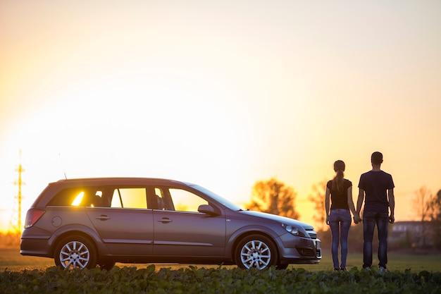 Młoda para, szczupła atrakcyjna kobieta z długim kucykiem i przystojny mężczyzna stojący przy srebrnym samochodzie w zielonym polu na jasnym niebie o zachodzie słońca lub wschodzie słońca